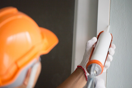 Construction workers install doors - windows and use silicon and sealant. 스톡 콘텐츠 - 96906367