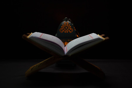 Quran - holy book of Muslims around the world, placed on a wooden board, black background 스톡 콘텐츠