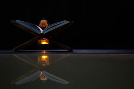 Koran - heiliges Buch der Muslime auf der ganzen Welt, auf einem Holzbrett, schwarzer Hintergrund