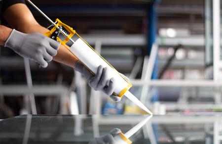 La mano degli uomini utilizza un adesivo siliconico con adesivo per collegare lo specchio con l'alluminio. Archivio Fotografico