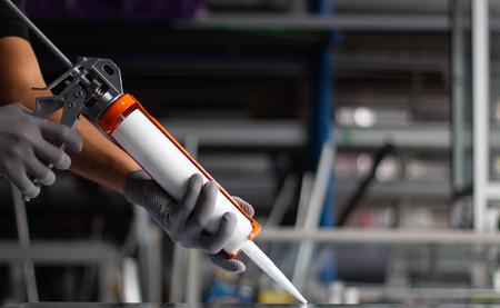 Männerhand verwendet Silikonkleber mit Klebstoff, um den Spiegel mit Aluminium zu verbinden.
