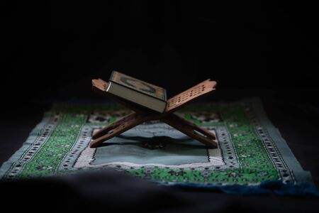 Quran - Muslim holy book placed on a wooden board