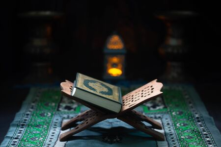 Corán - libro sagrado musulmán colocado sobre una tabla de madera Foto de archivo
