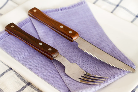Forks and  knives laid out on a plate. Stock fotó