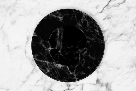 Black marble plate placed on white marble slab. Фото со стока