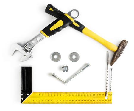 trabajando en casa: Casa Marco en forma con una sonrisa en el interior hecha por herramientas con copia espacio aislado en fondo blanco Foto de archivo