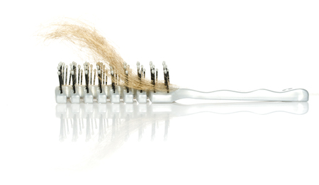 uncombed: Hairbrush with lock of hair loss and mirror reflection isolated on white background with copy space