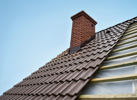 roofing: Rroof under constructions with lots of tile and red brick chimney