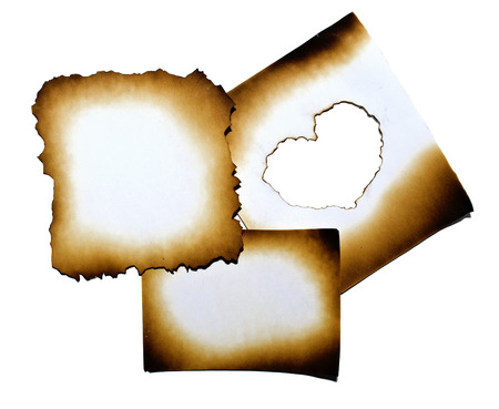 papel quemado: Collage de papel quemado con el corazón en el agujero quemado en el fondo blanco con trazado de recorte