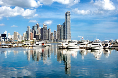 floating: Luxury yachts on the background of skyscrapers with water reflection - Panama City Stock Photo