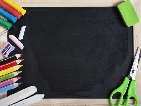 School supplies on wooden frame blackboard with wet empty surface. Plasticine, paintbrush, chalk, sharpener, crayons, scissors and eraser. Stock Photo