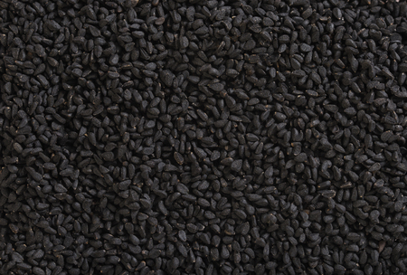 Black cumin background. Nigella sativa seed texture.