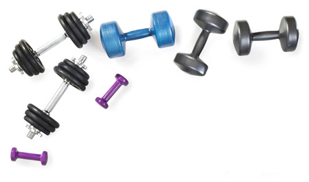 Different dumbbells composition on white background. Professional metal dumbbells and fitness dumbbells. Sport accessories. Top view. Frame. 写真素材