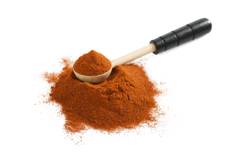 Pile of red ground paprika with wooden spoon isolated on white background. Heap of hot chili pepper.