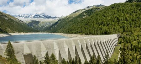 Big concrete dam with scenery of lake, forest and high mountains. Italy travel.