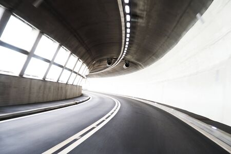 Blurry concrete tunnel with empty road. Curve on the road. Bend, turn. Banque d'images