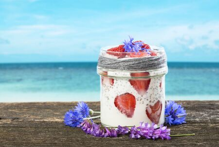 Healthy smoothie with chie seeds and fresh strawberries on rustic wood plank with tropical sea background. Homemade breakfast in jar with flowers.
