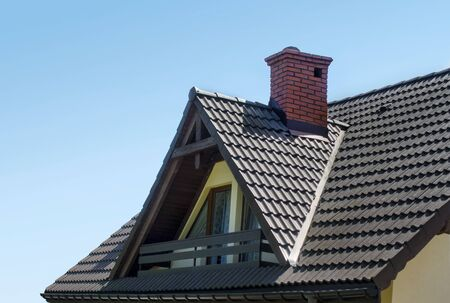 Roof with brown tiles, red chimney made by brick and attic with balcony against blue sky. House background.