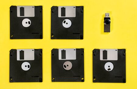 Floppy disk in row with standing out usb memory flash drive. Retro vs modern style on yellow background