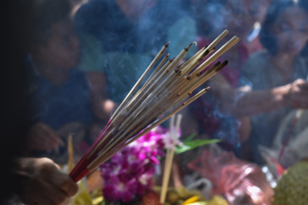 Incense sticks on joss stick pot are burning and smoke use for pay respect to the Buddha. Stock Photo