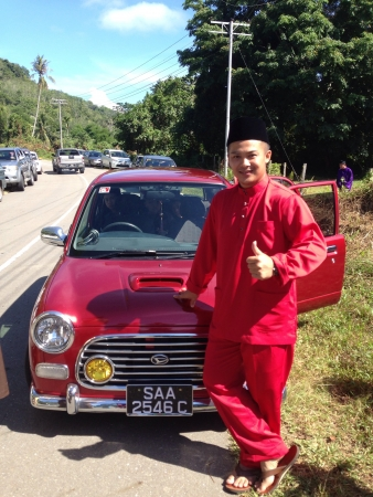 Malay man dressed in red posing with his car during Hari Raya celebration, Sabah, Malaysia