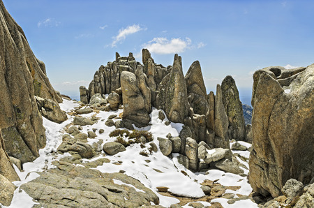 Landscape of rocky summit covered of snow and surrounded by crags photo