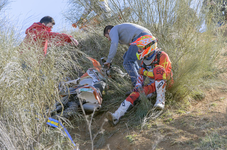 GUADALAJARA, SPAIN - FEBRUARY 22th 2015: Castilla-La Mancha cross country championship. Unknown people help to Heber Izat Gomez Hernandez after an accident with his KTM motorcycle, during first race of 2015, in Guadalajara, on February 22th 2015. (2 of 4) Editorial
