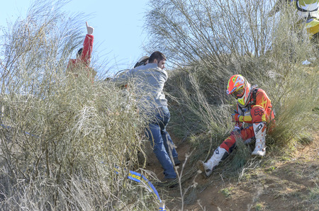 gomez: GUADALAJARA, SPAIN - FEBRUARY 22th 2015: Castilla-La Mancha cross country championship. Unknown people help to Heber Izat Gomez Hernandez after an accident with his KTM motorcycle, during first race of 2015, in Guadalajara, on February 22th 2015. (3 of 4)