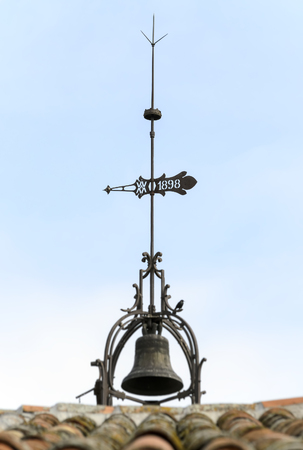 Top part of old bell tower with lightning rod and weather-vane over it photo