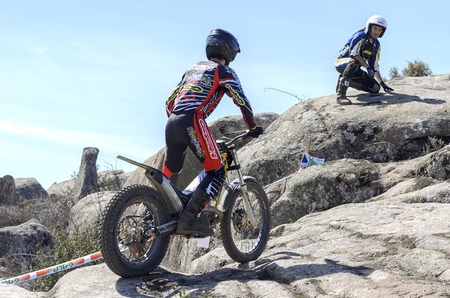 VALDEMANCO, SPAIN - MARCH 08th 2015: Madrid trial championship. Moment when unknown master biker is guiding to young biker, before he ascends through the rocks, during first race of season 2015, in Valdemanco, on March 08th 2015.