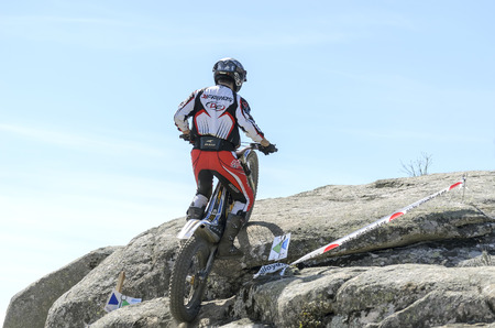 VALDEMANCO, SPAIN - MARCH 08th 2015: Madrid trial championship. Moment when unknown biker is jumping over granite rocks, during first race of season 2015, in Valdemanco, on March 08th 2015.