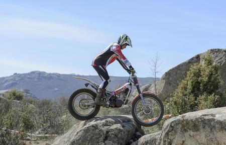 VALDEMANCO, SPAIN - MARCH 08th 2015: Madrid trial championship. Moment when unknown biker is going through a rock, during first race of season 2015, in Valdemanco, on March 08th 2015.