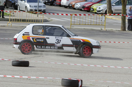 he is public: MEJORADA DEL CAMPO, SPAIN - MARCH 29th 2015: Car rally, of slalom, at public street. Leopoldo Sanchez Lopez with his Peugeot 205 1.9 GTI, in Mejorada del Campo, on March 29th 2015. He finished in third position -Novice ranking-. Editorial