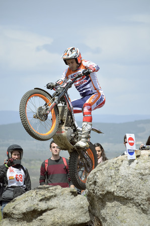 LOZOYUELA, SPAIN - APRIL 12th 2015: Spain trial championship. Unknown people are looking at Toni Bou, when he is jumping over granite rocks, in Lozoyuela, on April 12th 2015. He won the race.