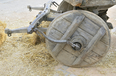 Wheel of an old covered wagon, surrounded with dry straw over the floor Stock Photo