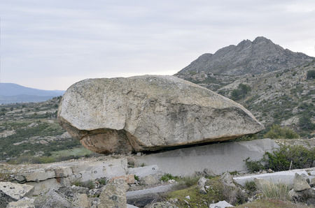 singular: Singular and large rock located in an environment of rock mountains Stock Photo