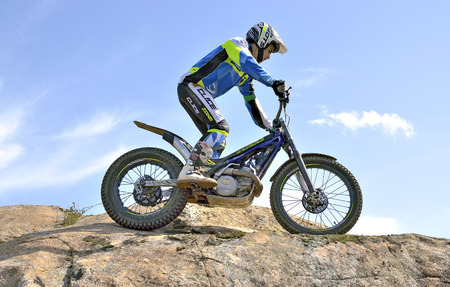 LOZOYUELA, SPAIN - APRIL 12th 2015: Spain trial championship. Moment when, unkonown motorcyclist is driving over a large granite rock, in Lozoyuela, on April 12th 2015.