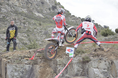 LOZOYUELA, SPAIN - APRIL 12th 2015: Spain trial championship. Unknown people are looking at Jeroni Fajardo, when he is jumping over granite rocks, in Lozoyuela, on April 12th 2015. He finished in 2nd position (TR1).