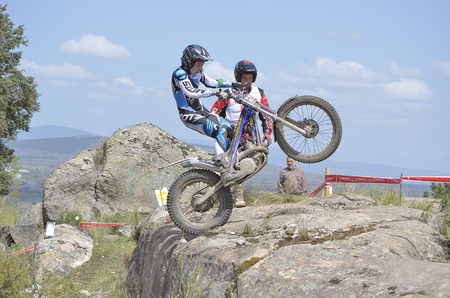 LOZOYUELA, SPAIN - APRIL 12th 2015: Madrid trial championship. Unknown people looking at Alen Damil when he is driving over a granite rock, after a jump, in Lozoyuela, on April 12th 2015. He finished 7th (Junior level).