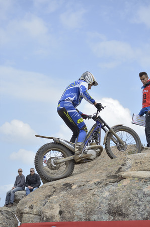 joaquin: LOZOYUELA, SPAIN - APRIL 12th 2015: Spain trial championship. Unknown people are looking at Joaquin Salcedo, after he has jumped over granite rocks, in Lozoyuela, on April 12th 2015. He finished 2nd (TR2).