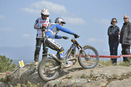 LOZOYUELA, SPAIN - APRIL 12th 2015: Madrid trial championship. Unknown people looking at unkonown motorcyclist when he is driving over a granite rock, after a jump, in Lozoyuela, on April 12th 2015.
