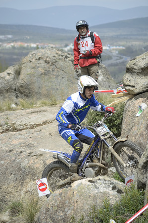 joaquin: LOZOYUELA, SPAIN - APRIL 12th 2015: Spain trial championship. Unknown man is timing to Joaquin Salcedo, while he is going to jump over granite rocks, in Lozoyuela, on April 12th 2015. He finished 2nd (TR2).