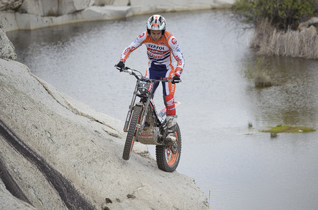 LOZOYUELA, SPAIN - APRIL 12th 2015: Spain trial championship. The world champion, Toni Bou, drives his motorcycle over rocks near a pond, in Lozoyuela, on April 12th 2015. He won the race (TR1 level).