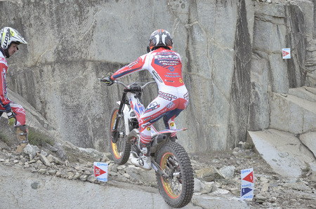 LOZOYUELA, SPAIN - APRIL 12th 2015: Spain trial championship. Unknown man is looking at Jeroni Fajardo, when he is jumping over granite rocks, in Lozoyuela, on April 12th 2015. He finished in 2nd position (TR1).