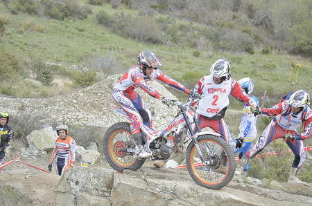 LOZOYUELA, SPAIN - APRIL 12th 2015: Spain trial championship. Toni Bou and other unknown people are looking at Jeroni Fajardo, when he is jumping over granite rocks, in Lozoyuela, on April 12th 2015. He finished in 2nd position (TR1).