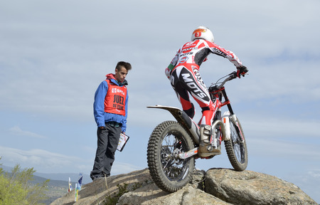 LOZOYUELA, SPAIN - APRIL 12th 2015: Spain trial championship. Unknown judge looking at, the moment when, Gabriel Marcelli is going through a rock, in Lozoyuela, on April 12th 2015. He won the race (Junior level).