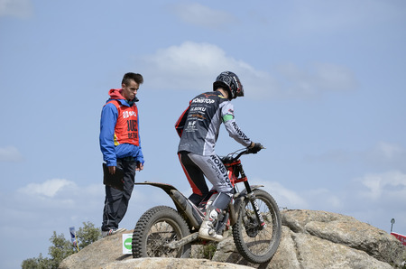 adria: LOZOYUELA, SPAIN - APRIL 12th 2015: Spain trial championship. Unknown judge looking at, the moment when, Adria Albejano is going through a rock, in Lozoyuela, on April 12th 2015. He finished 3rd (TR3 level).
