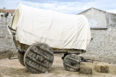 covered wagon: Vintage covered wagon used to transport straw, people and others things in western time