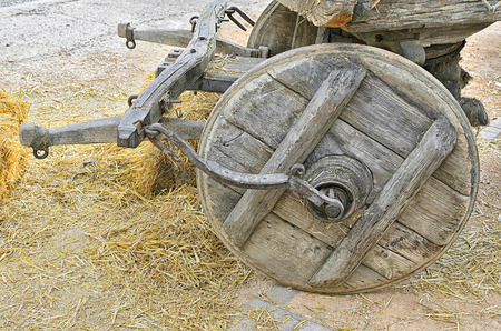 covered wagon: Wheel of an old covered wagon, surrounded with dry straw over the floor Stock Photo