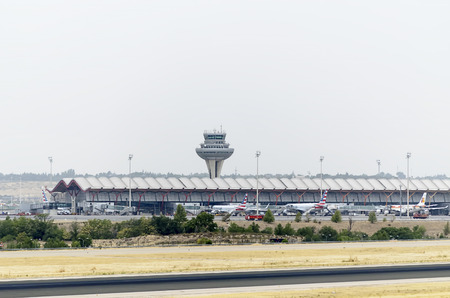 control tower: MADRID, SPAIN - AUGUST 8th 2015: Cloudy day. View of passenger terminal and control tower, in Madrid-Barajas -Adolfo Suarez- airport, with aircrafts parked, on August 8th 2015. Editorial